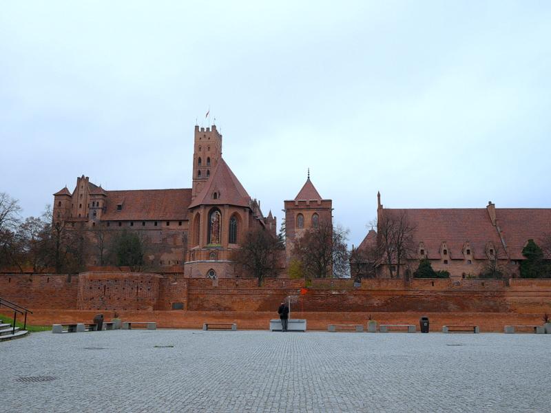 グダニスク ポーランド マルボルク城 タンネンベルクの戦い 北の十字軍 マリーエンブルク ドイツ騎士団   パネルの背後にひかえる現在のマルボルク城 @Zamek w Malborku
